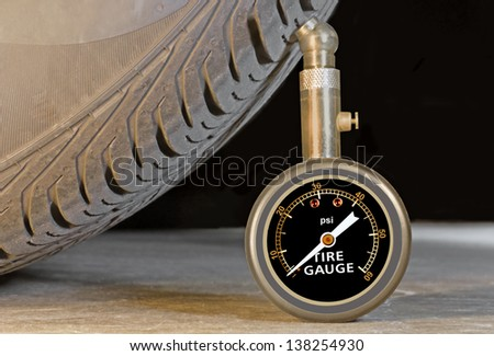 Car tire pressure gauge, tire tread and sidewall close up. Pressure meter stands upright against tire profile on a grey concrete floor. Black background. - stock photo