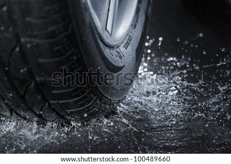 Car tire splashing in water. - stock photo