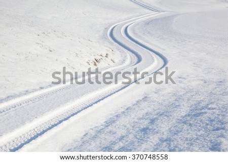 Car tire track on a empty winter road - stock photo