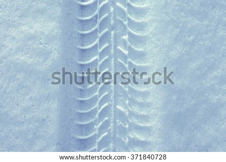 Car tire tracks in the snow - stock photo