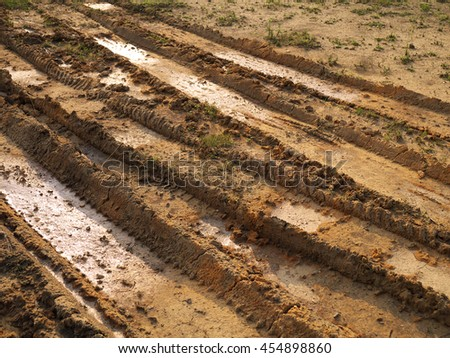 Car tire tracks in yellow sandy mud