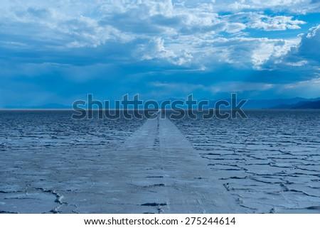 Car tire tracks on Bonneville Salt Flats at sunset, Tooele, Utah, USA. - stock photo
