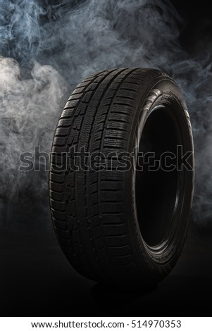 Car tires close-up Winter wheel profile structure on black background with smoke