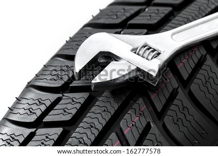 Car tires close-up with Wrench tool Winter wheel profile structure on white background