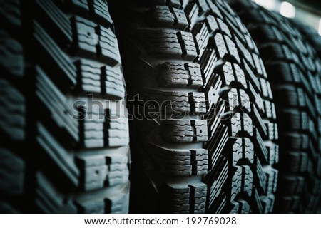 Car tires in a row on a shelf tire