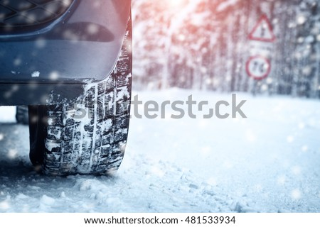 car tires on winter road covered with snow vehicle on snowy alley in the morning
