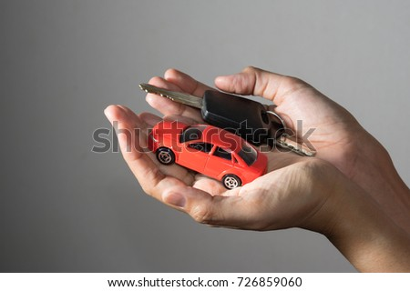 Car toy and key in woman hand.