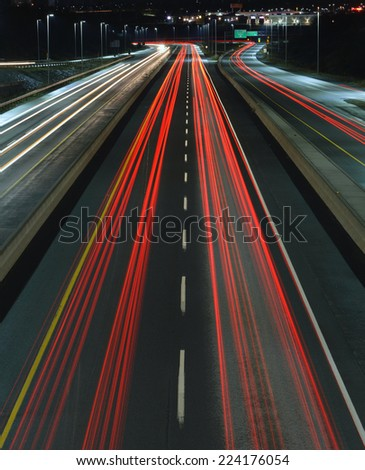 Car trails on a busy highway at night. - stock photo