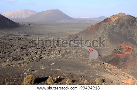 Car traveling between volcano hills - stock photo