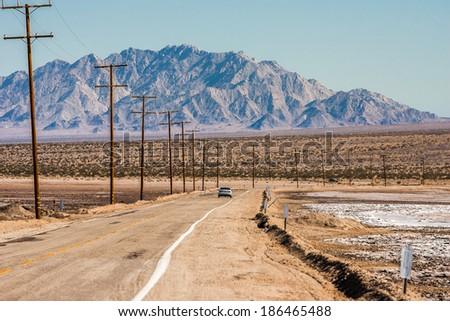 Car travels along a desert road between two salt lakes. - stock photo