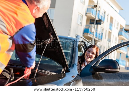 Car troubles woman starting cables broken vehicle on the road - stock photo