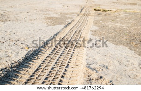Car tyre track on sandy beach.