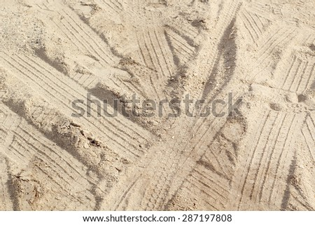 car tyre tracks on the beach sand in perspective - square image - stock photo