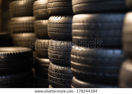 Car tyres stacked in a tyre distribution centre - stock photo