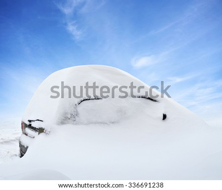 Car under deep snow in winter day after snowfall. Blue sky on background - stock photo