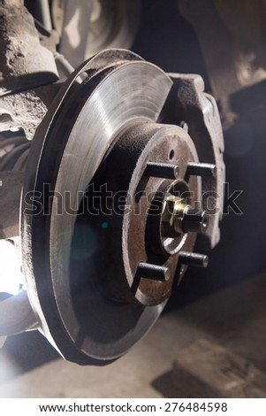 Car under repair on hoist at service station. - stock photo