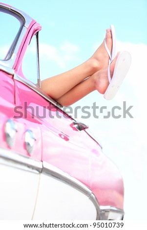 Car vacation holiday road trip. Travel and freedom happy lifestyle concept image of pink vintage retro car with woman feet during fun summer holidays.