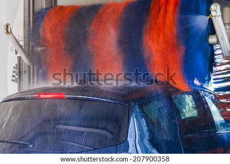 Car wash, black car in automatic car wash, rotating red and blue brushe. Washing vehicle. - stock photo