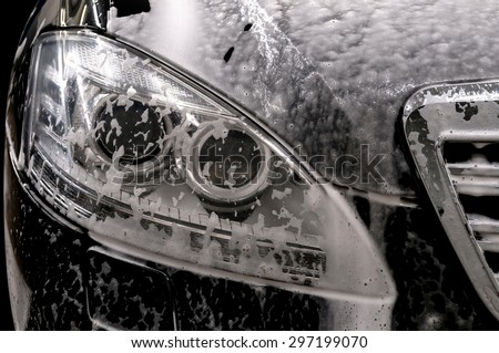 Car wash with soap. Modern auto covered by foam. - stock photo