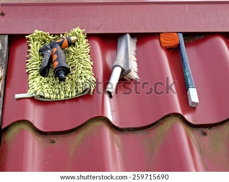 Car washing brushes and sprinkler on well metal roof       - stock photo