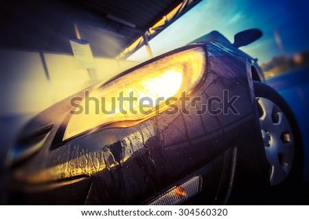 Car Washing Closeup. Modern Car Inside Car Wash Headlight Closeup. - stock photo