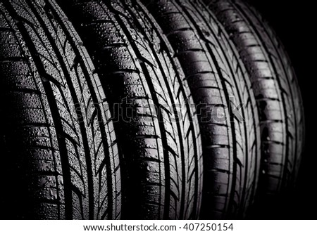 Car wet tyres on a black background. - stock photo