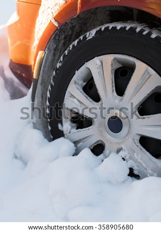Car wheel covered with snow in winter. - stock photo
