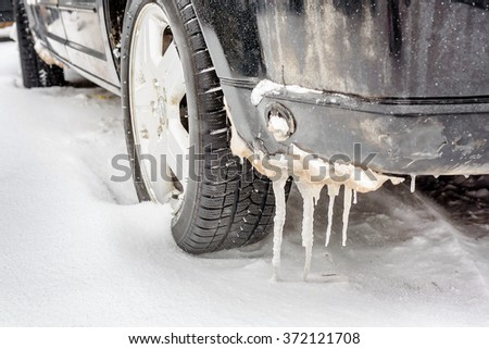 Car wheel covered with snow on a winter day - stock photo