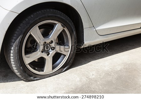 car wheel flat tire on the road - stock photo