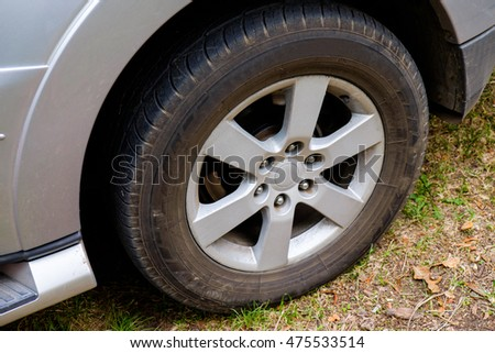 Car wheel on a road. Off-road tire. Outdoor, adventures and travel suv. Close-up of car wheel on road in countryside with forest in background.