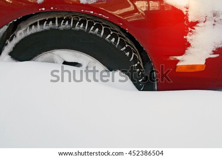 Car wheel stuck in the deep snow after the heavy snowstorm. - stock photo