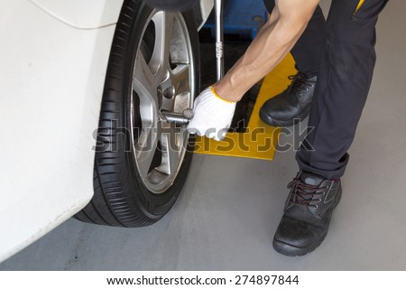car wheel tire replacement on floor by mechanic in the garage - stock photo