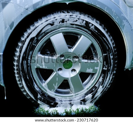 car wheel.Washing the car a jet of pure water on a background of green water. - stock photo