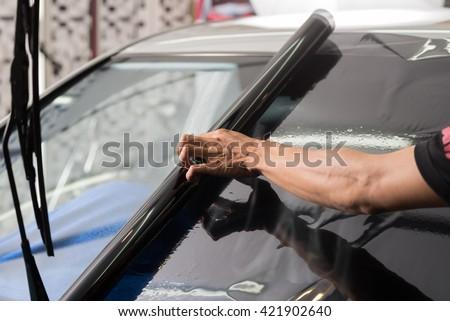 Car window tinting series : Installing car window tint - stock photo