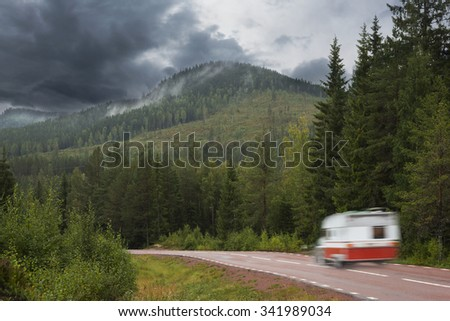 Car with caravan in gloomy scandinavian rural mountain landscape - stock photo