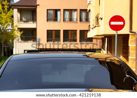 Car with dark tinted windows in an urban street below colorful apartment blocks and a no entry sign, close up view of the windshield - stock photo