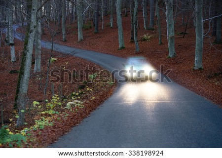 Car with headlights on narrow winding country road in beech forest at night - stock photo