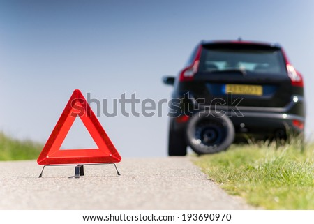 Car with problems and a red triangle to warn other road users - stock photo