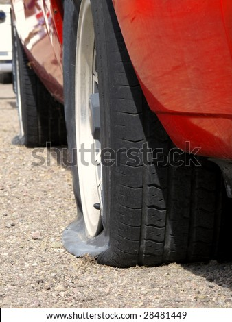 Car with two flat tires on roadside - stock photo