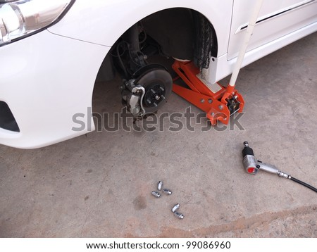 Car without tire at jack in service - stock photo