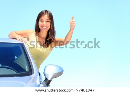 Car. Woman driver happy smiling showing thumbs up coming out of car window on blue summer sky above the clouds. Beautiful young mixed race Caucasian / Chinese Asian woman.