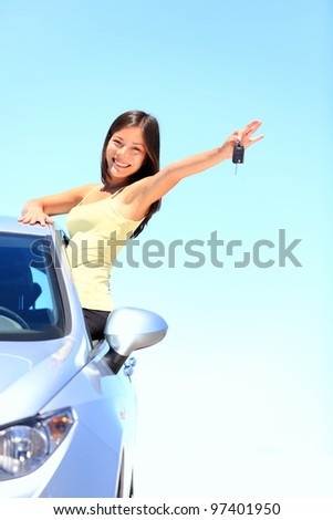Car. Woman driver showing car keys smiling happy in her new car. Beautiful young multiracial Caucasian / Chinese Asian female driver driving on spring or summer day. - stock photo