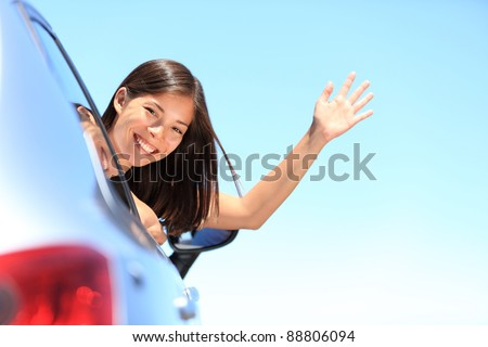 Car woman happy waving smiling at camera popping head out the window. New car, road trip vacation or drivers license concept. Beautiful young mixed race Chinese Asian / white Caucasian woman.