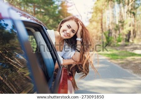Car woman on road trip. Happy smiling out the window - stock photo