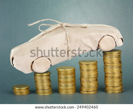 Car wrapped in paper standing on stack of coins on gray background - stock photo