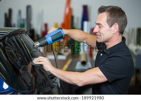 Car wrapper tinting a vehicle window with foil - stock photo
