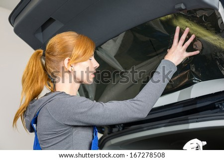 Car wrappers tinting a vehicle window with a tinted foil or film using heat gun and squeegee - stock photo