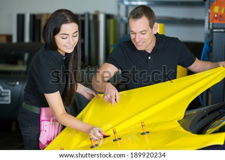 Car wrapping specialists straightening vinyl foil or film to remove ari bubbles - stock photo