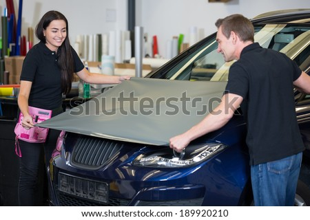 Car wrapping specialists wrapping a vehicle with grey vinyl film or foil - stock photo