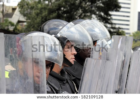 CARACAS, VENEZUELA - MARCH 16, 2014: State police blocking the passage of the protesters who claim for violations of human rights and the killing of civilians in peaceful demonstrations - stock photo